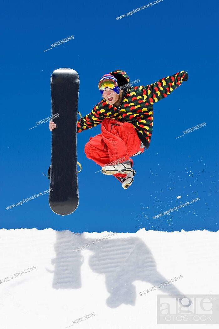 Stock Photo: A snowboarder leaps from the side of a half pipe in celebration.