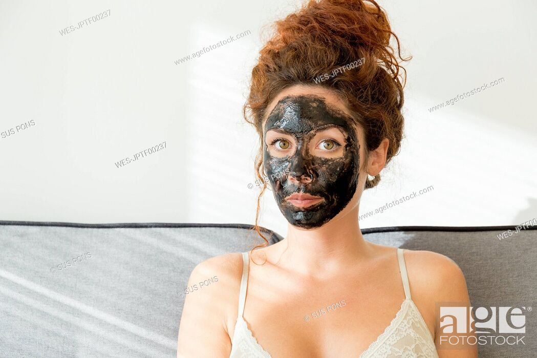 Stock Photo: Portrait of young woman wearing facial mask at home.