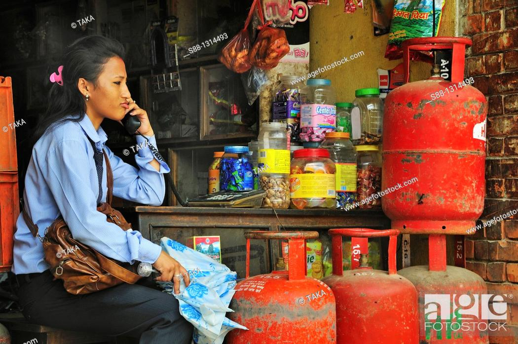 Stock Photo: School girl talking on the phone at the shop.
