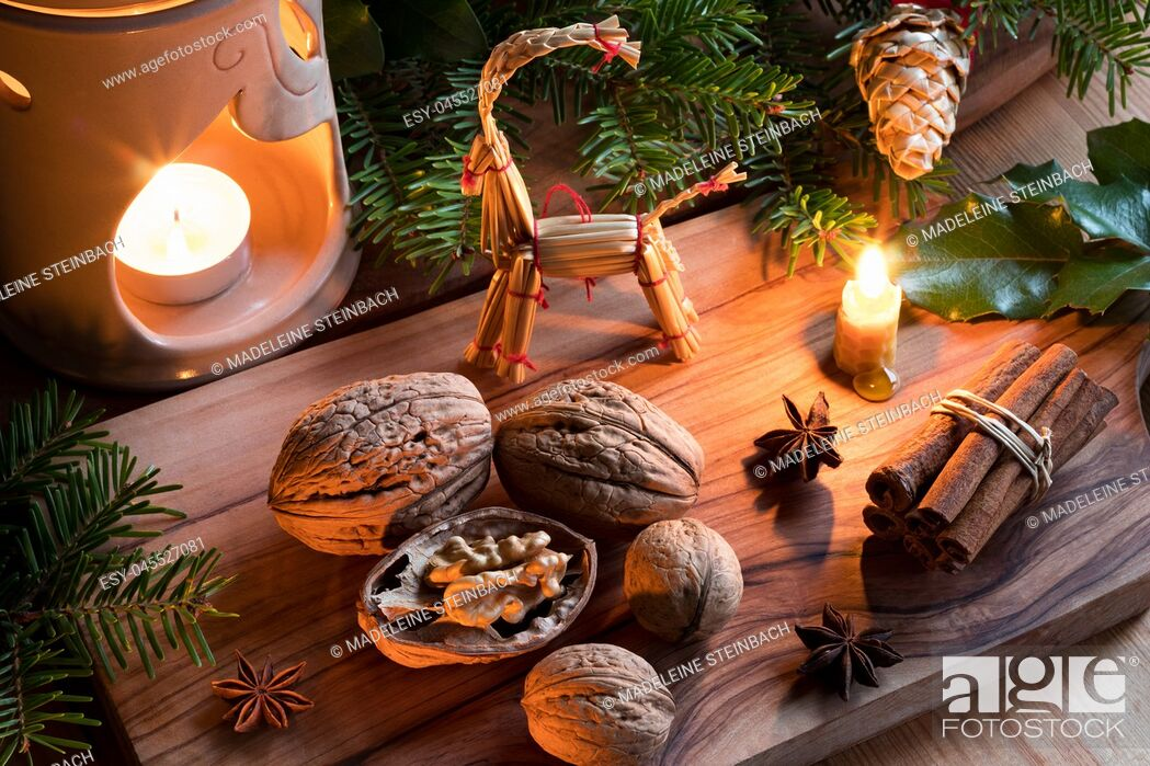 Stock Photo: Christmas decoration - walnuts, candles, cinnamon sticks, star anise, fir branches, and straw ornaments.