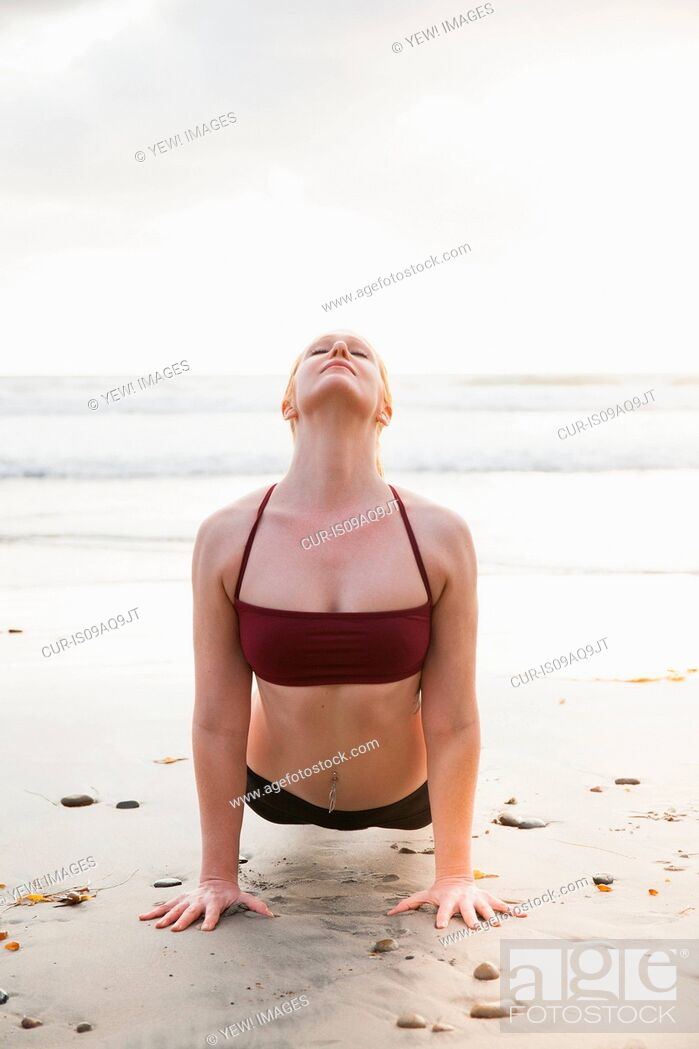 Imagen: Mid adult woman practicing plank yoga pose on beach.