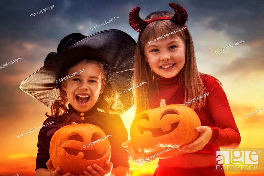 Imagen: Two happy sisters on Halloween. Funny kids in carnival costumes outdoors. Cheerful children and pumpkins on sunset background.