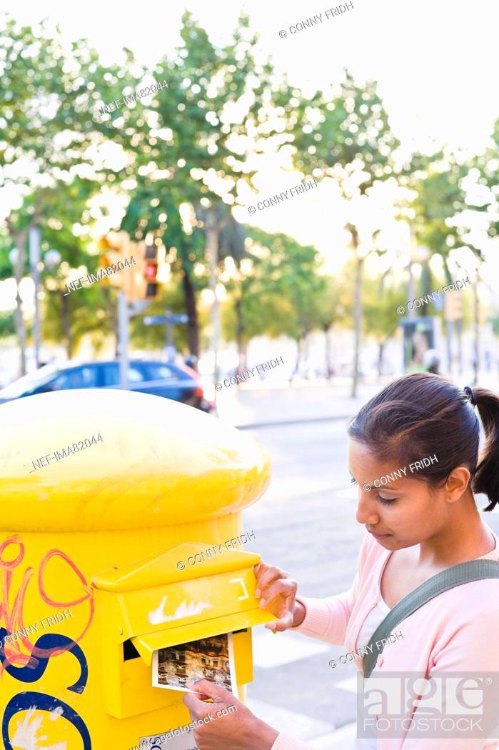 Stock Photo: Woman posting postcard to postbox.