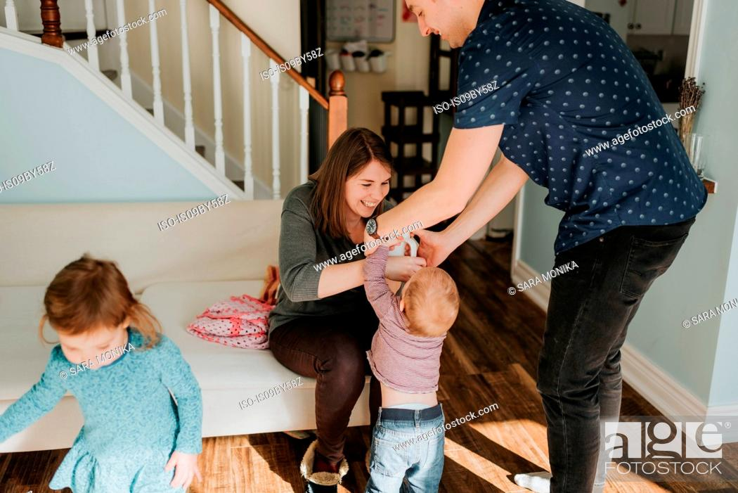 Stock Photo: Mid adult couple with baby boy and female toddler in living room.