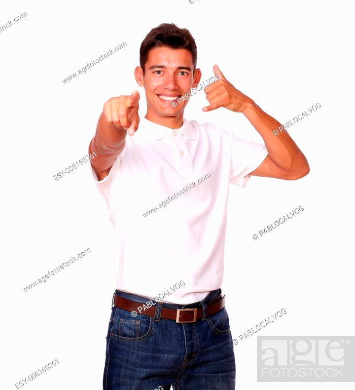 Stock Photo: Handsome man in a studio, is smiling and pointing at you with a calling sign, on a white background.