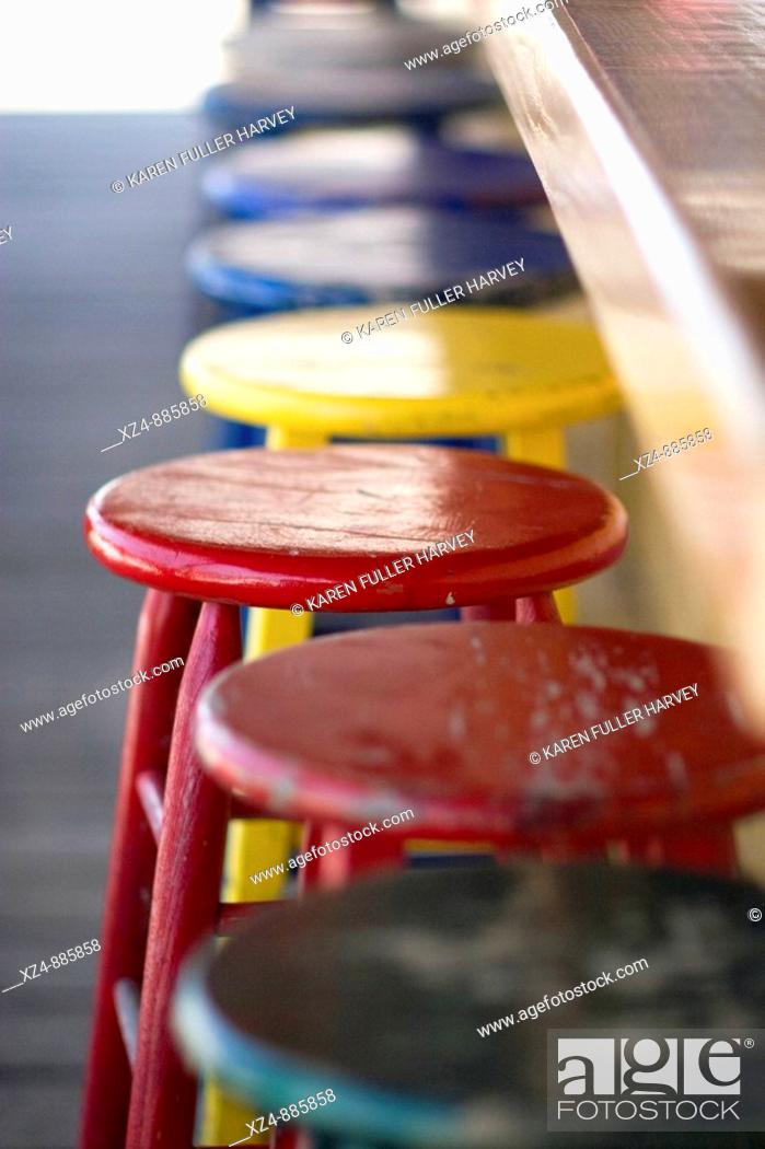 Stock Photo: primary colored stools await bar patrons at an outside beach bar.