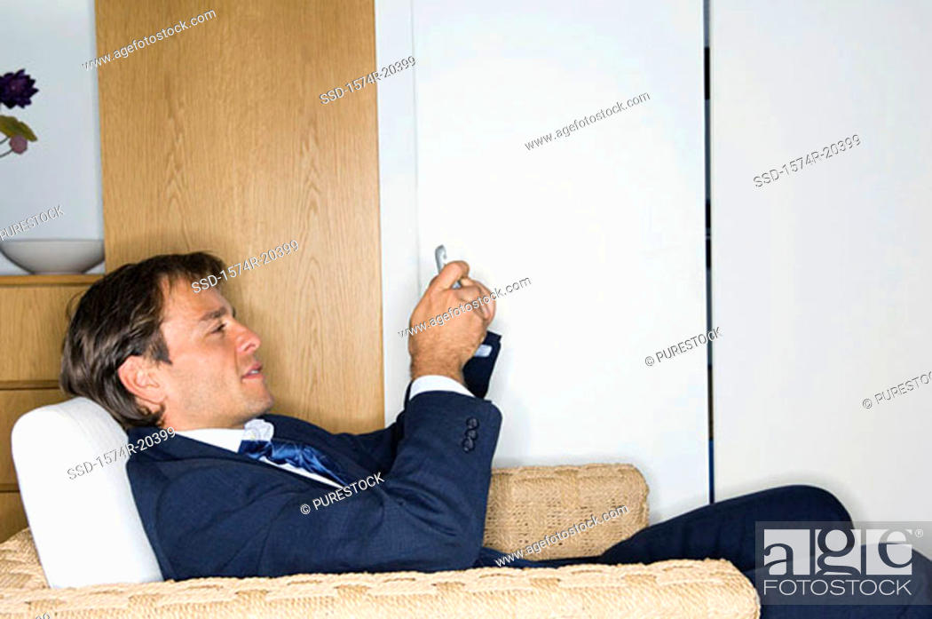 Stock Photo: Side profile of a businessman sitting in an armchair and holding a mobile phone.