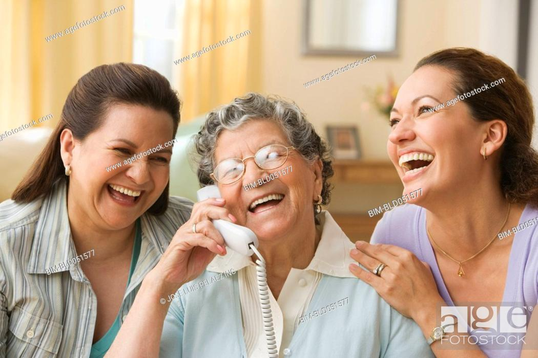 Stock Photo: Hispanic grandmother, mother and daughter with telephone.