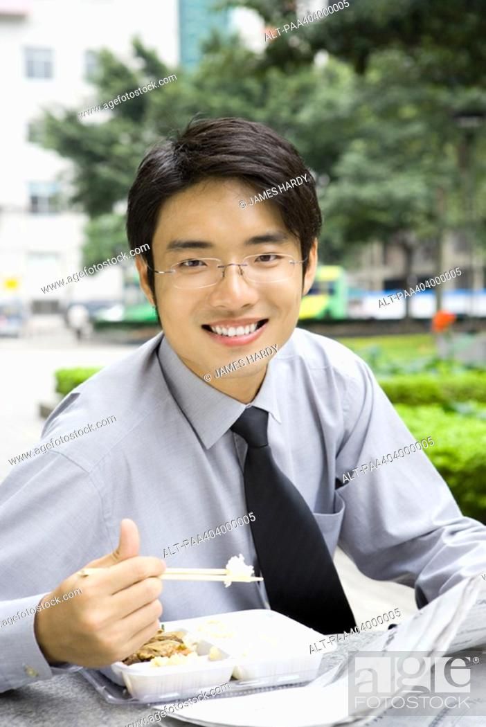 Stock Photo: Young businessman eating takeout food outdoors.