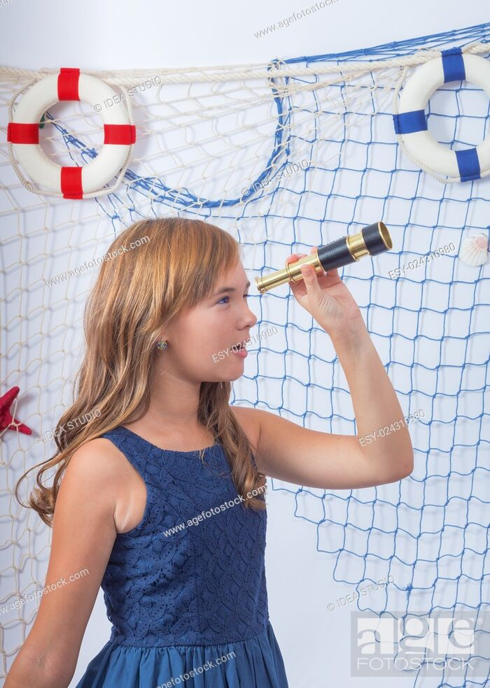 Stock Photo: Beautiful teen girl in blue dress looking at telescope.