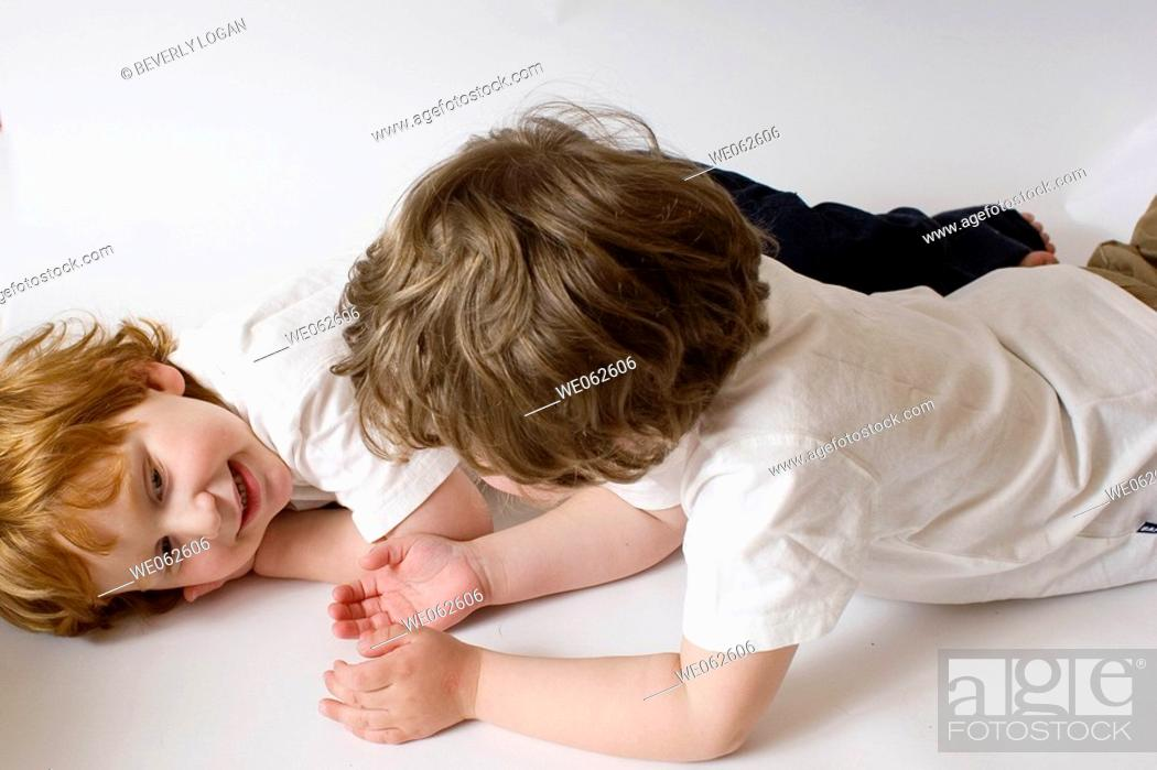 Stock Photo: Two three-year-old boys lying down and talking.
