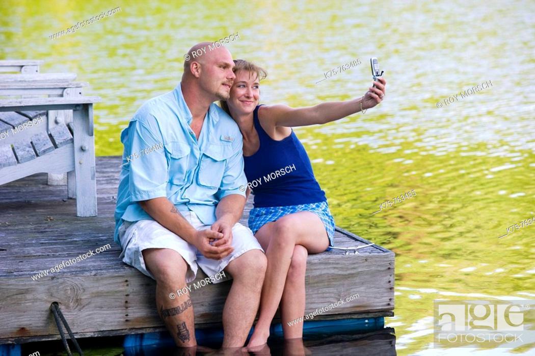 Stock Photo: couple on dock taking photo with camera phone.