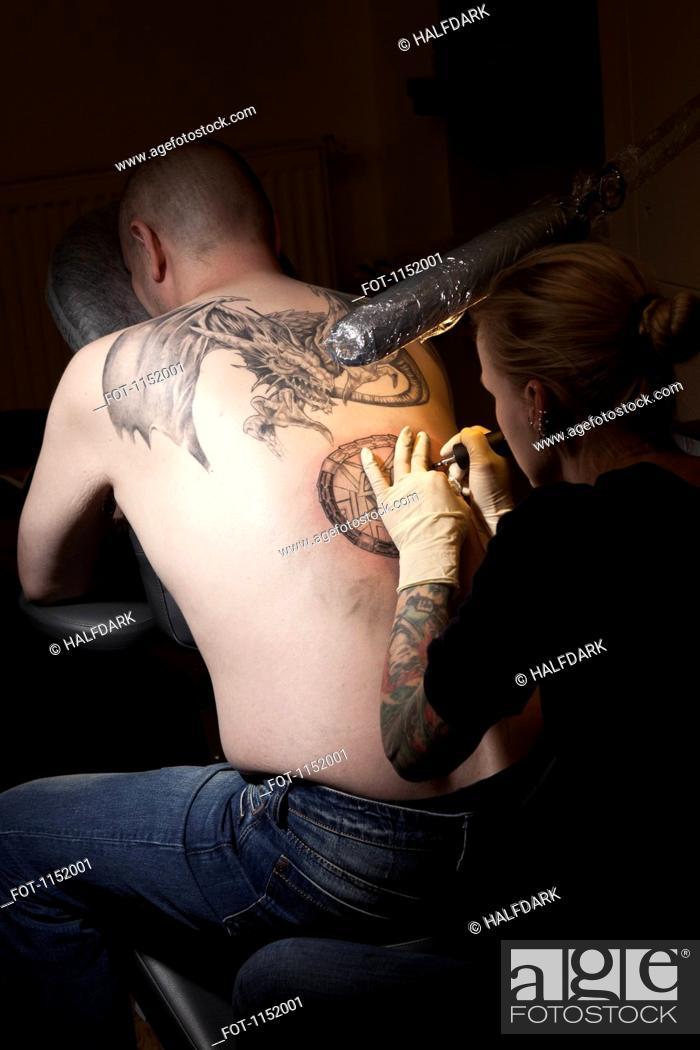 Stock Photo: A female tattoo artist tattooing a man's back in a tattoo shop.