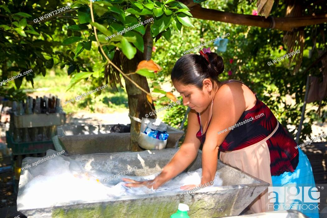 Stock Photo: Young woman washing clothes, Papantla, Veracruz, Mexico.