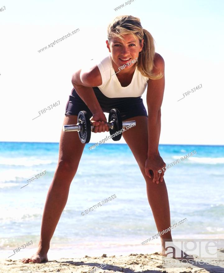 Stock Photo: Woman in sportswear on the beach practising with dumbbell.