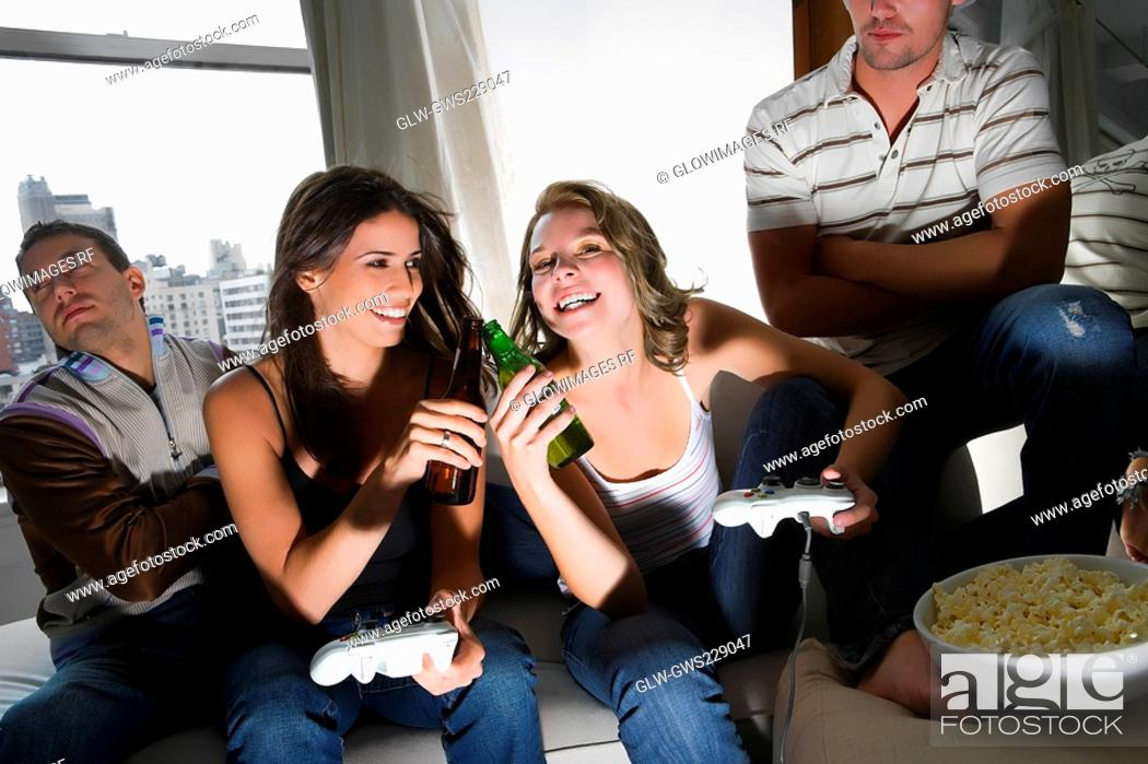 Stock Photo: Two young women toasting with beer bottles and two young men sitting beside them.