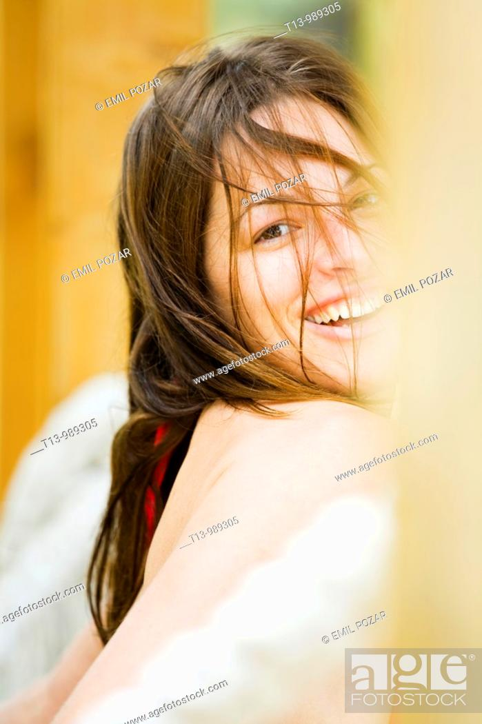 Stock Photo: Smiling attractive young woman portrait with untidy hair.