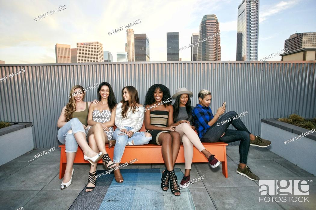 Stock Photo: A group of young women partying on a city rooftop at dusk.