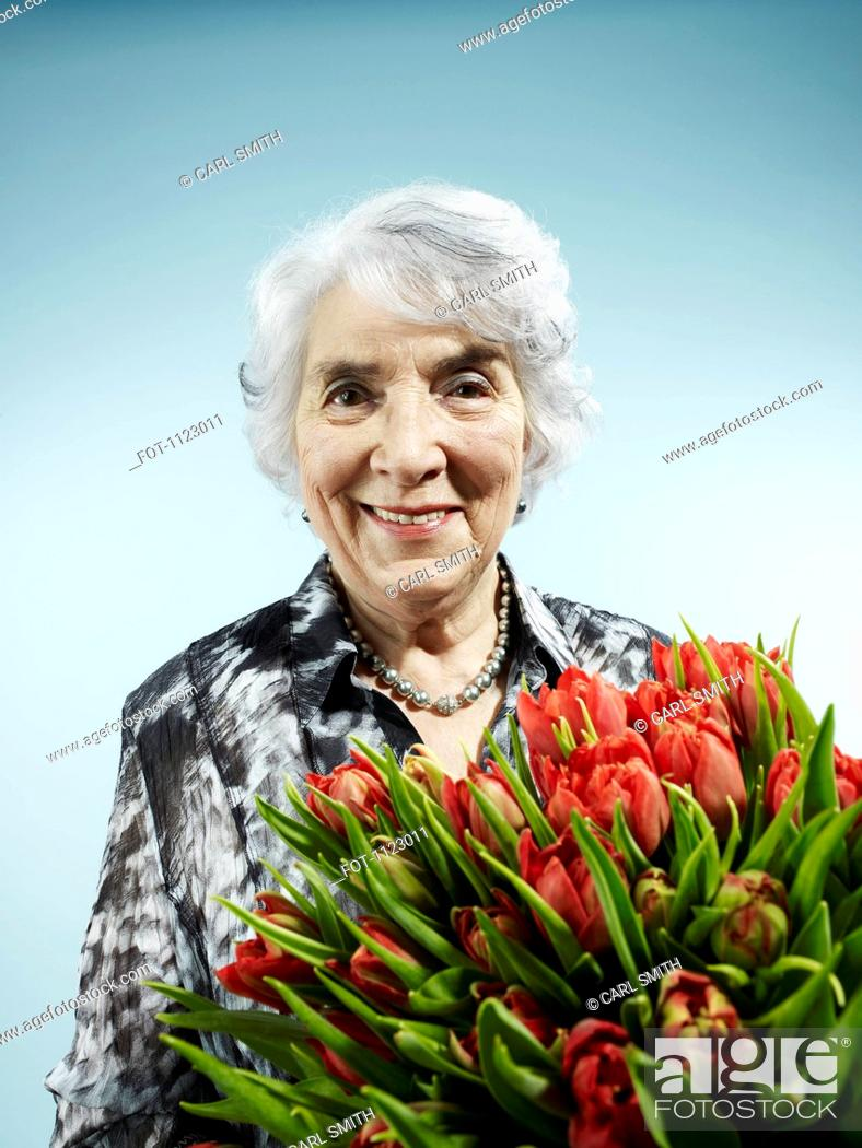 Stock Photo: A senior woman receiving a bouquet of tulips.