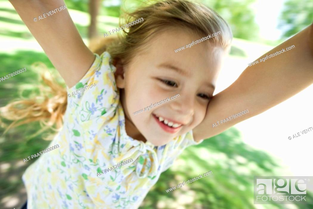 Stock Photo: Little girl being spun by arms outdoors.