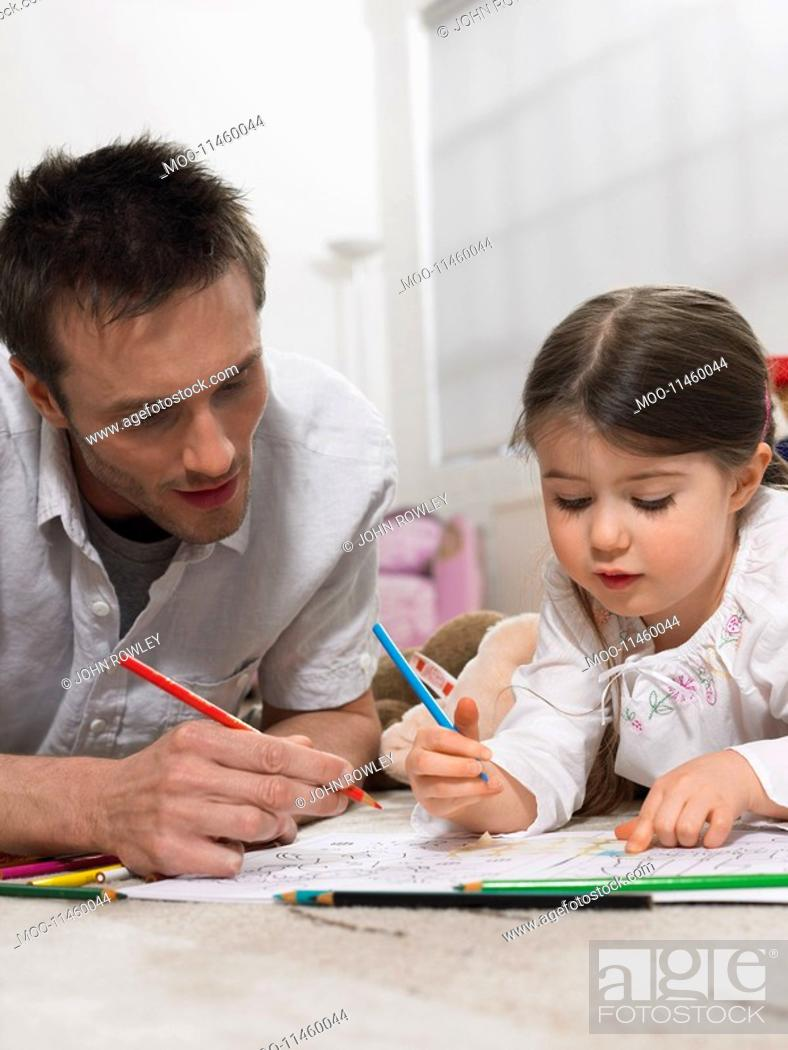 Stock Photo: Father and daughter 3-4 colouring in book on floor.