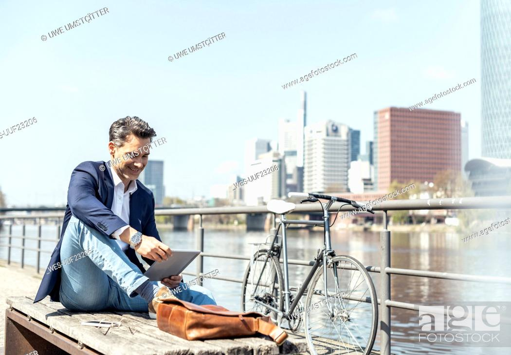 Stock Photo: Mature businessman using digital tablet on sunny day.