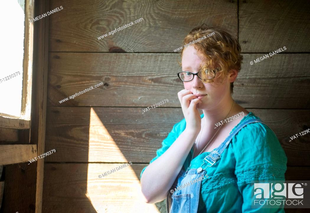 Imagen: Portrait of a girl with curly red hair and eyeglasses standing against an old, wooden barn wall; Pittsboro, North Carolina, United States of America.