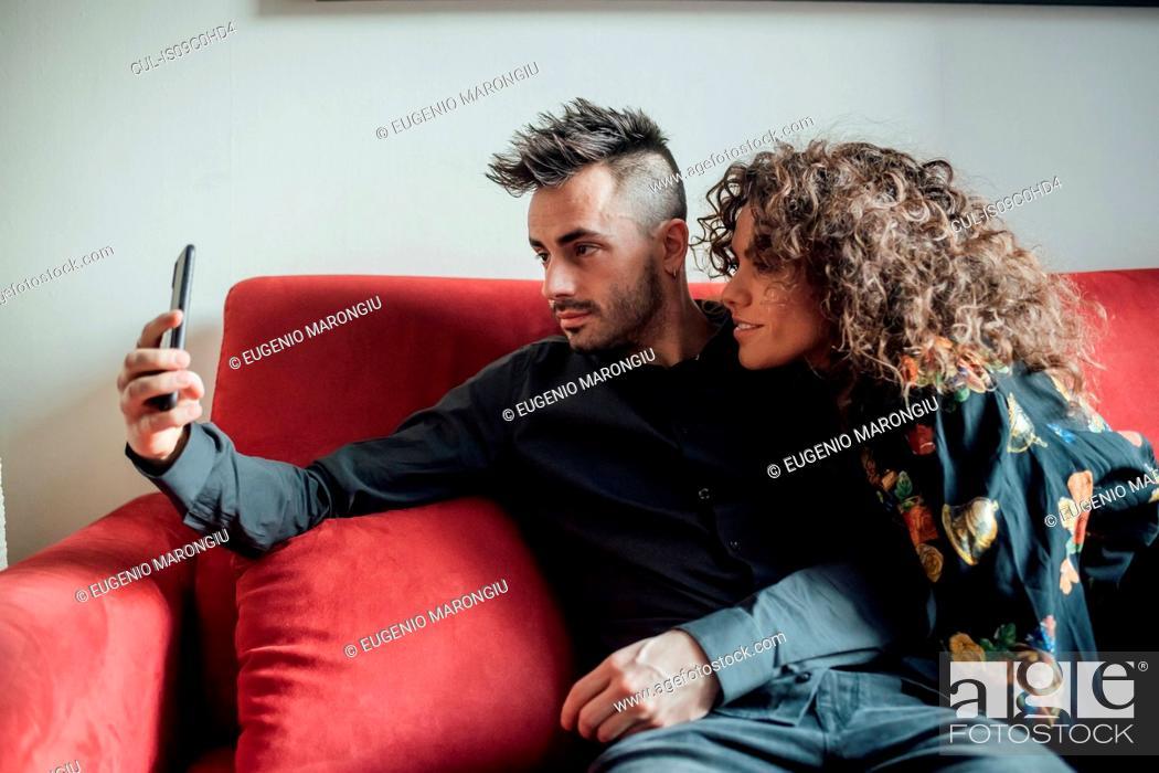 Stock Photo: Couple taking selfie on sofa.