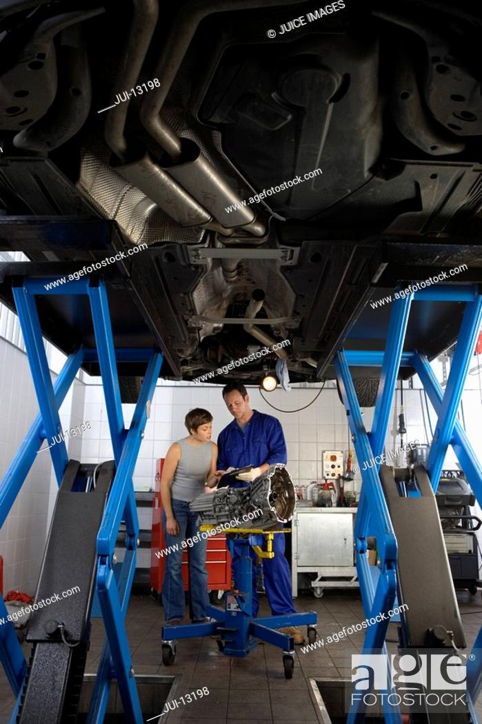Stock Photo: Mechanic showing clipboard to woman by elevated car, low angle view.