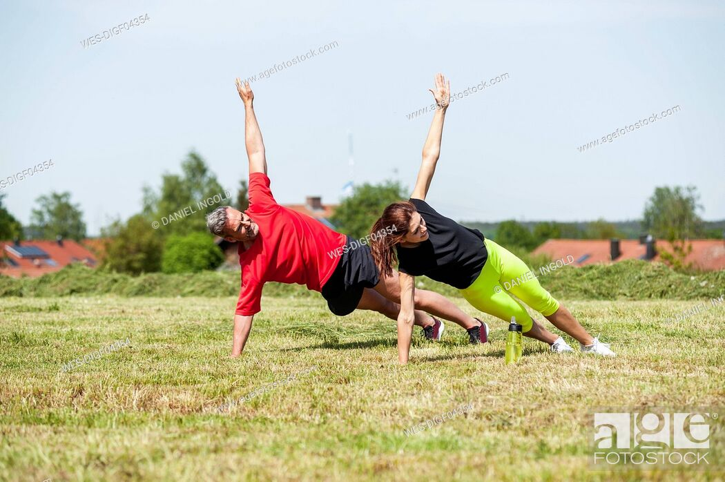 Stock Photo: Couple doing side plank exercise on meadow.