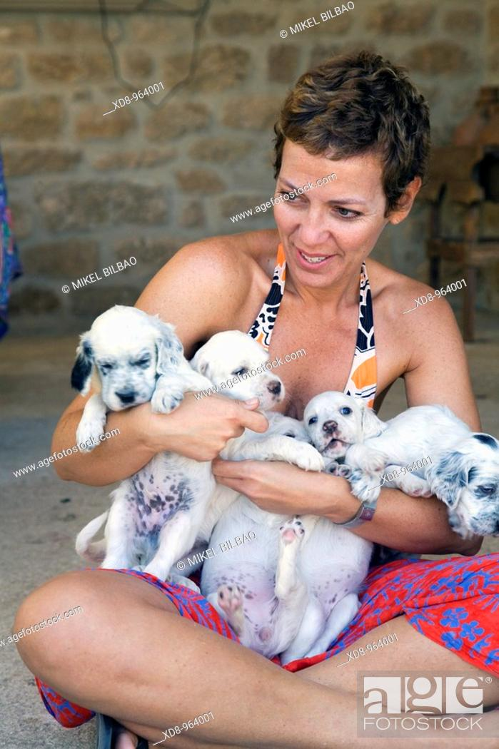 Stock Photo: young girl with a dog puppies of the English Setter breed.