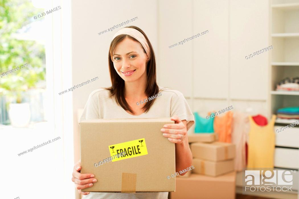 Stock Photo: Woman carrying box with fragile sticker into new house.
