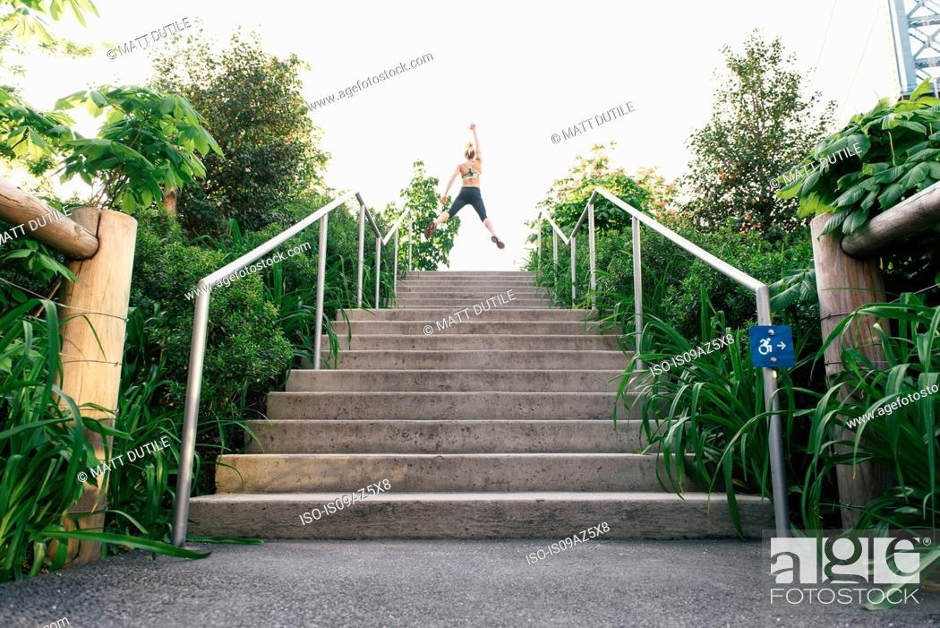 Imagen: Young woman exercising outdoors, at top of steps, Brooklyn Bridge Park, Brooklyn, New York, USA.