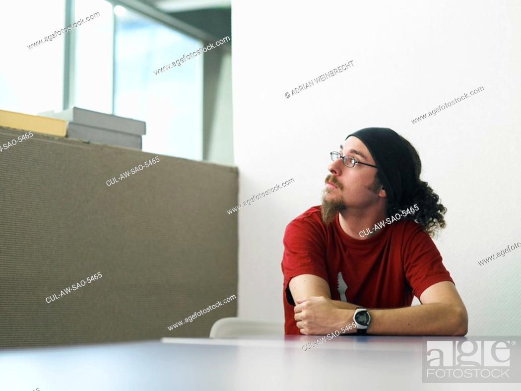 Stock Photo: Young man sitting at desk portrait.