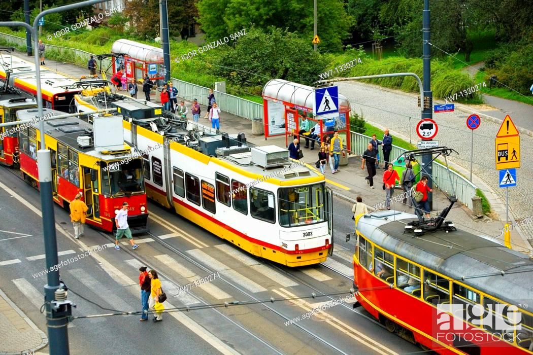 Stock Photo: People walking and driving their cars while the tram car races around the city of Warsaw, Poland.