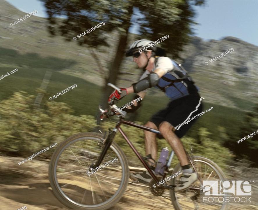 Stock Photo: A man riding his bike on a trail.