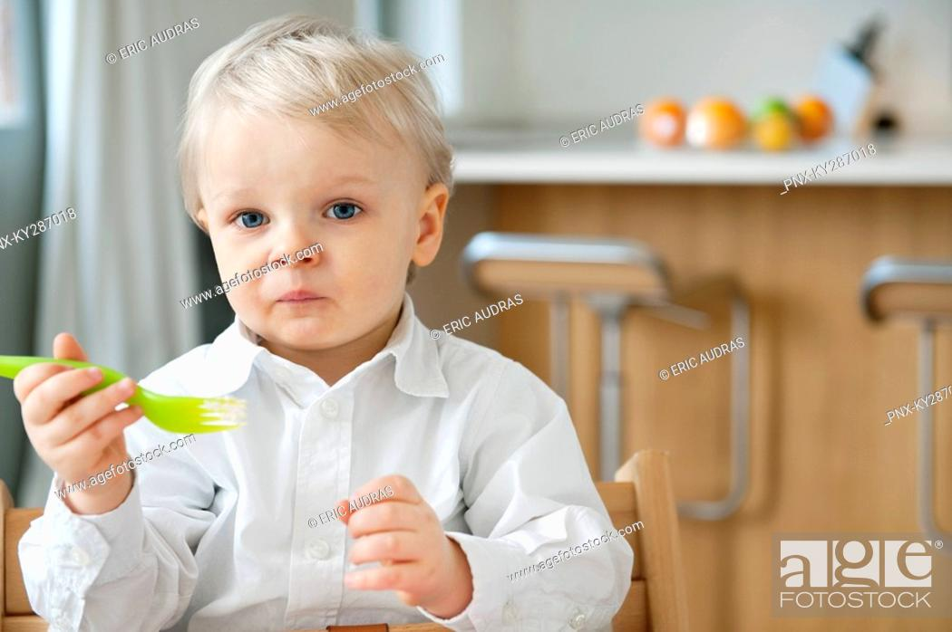 Stock Photo: Boy eating with a fork and making a face.
