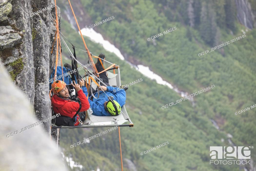 Photo de stock: Portrait of rock climbers using portaledge during climbing trip.