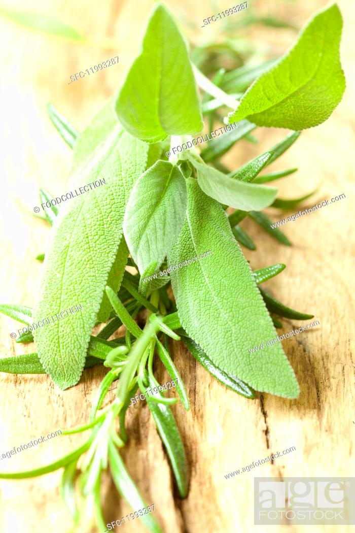 Stock Photo: Fresh sage and rosemary on a wooden surface.