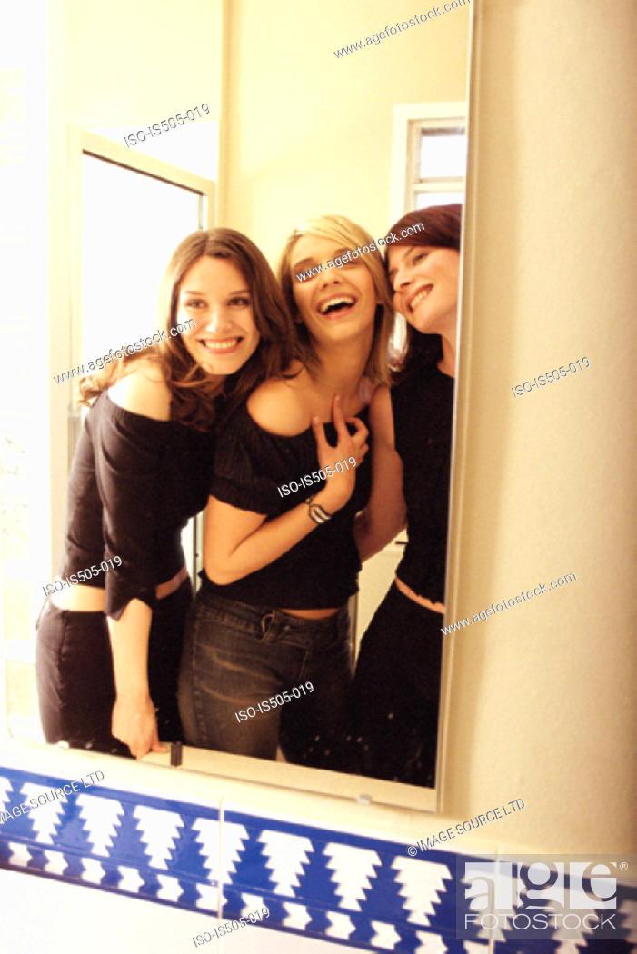 Stock Photo: Women joking around in bathroom.