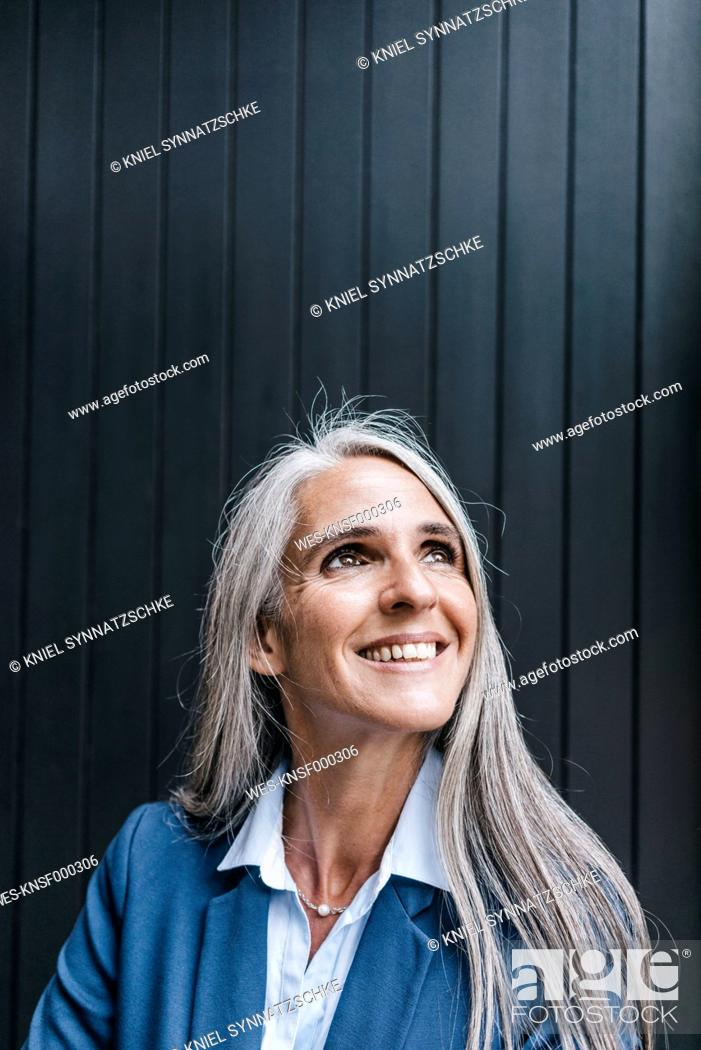Stock Photo: Portrait of smiling woman with long grey hair looking up.