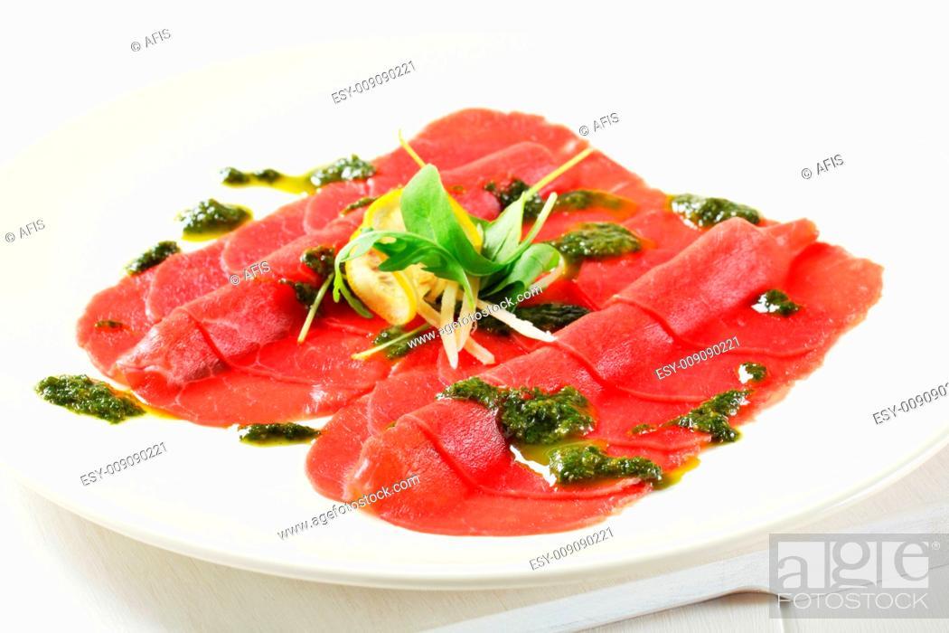 Stock Photo: Beef Carpaccio with pesto sauce and shavings of Parmesan.