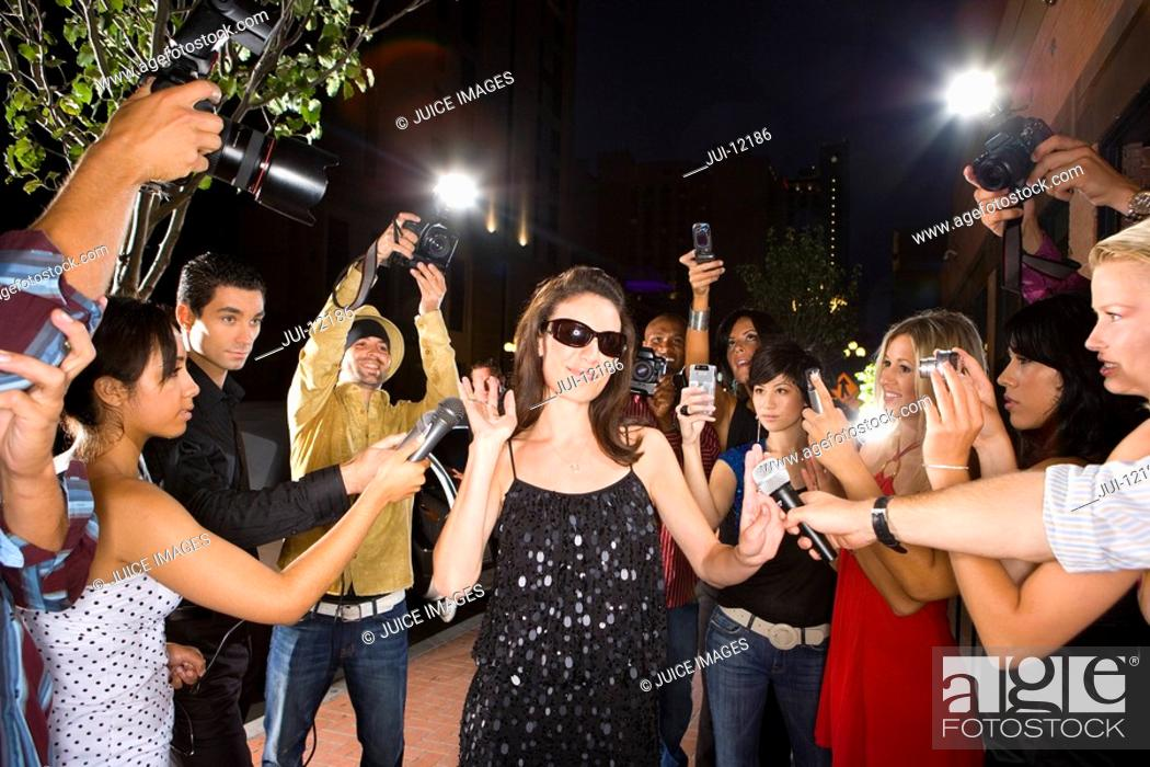 Stock Photo: Paparazzi taking photographs of young woman in sunglasses, low angle view.
