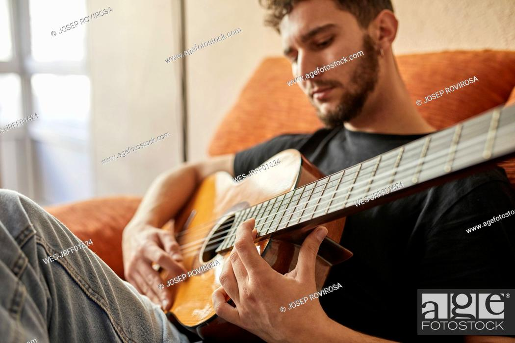 Imagen: Man playing guitar on couch.
