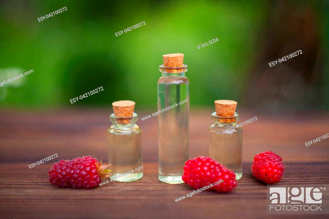 Stock Photo: Essence of Wild raspberries on a table in a beautiful glass Bottle.