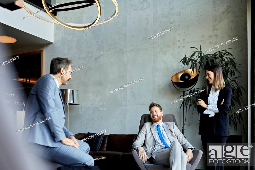 Stock Photo: Business people having a meeting in hotel lobby.