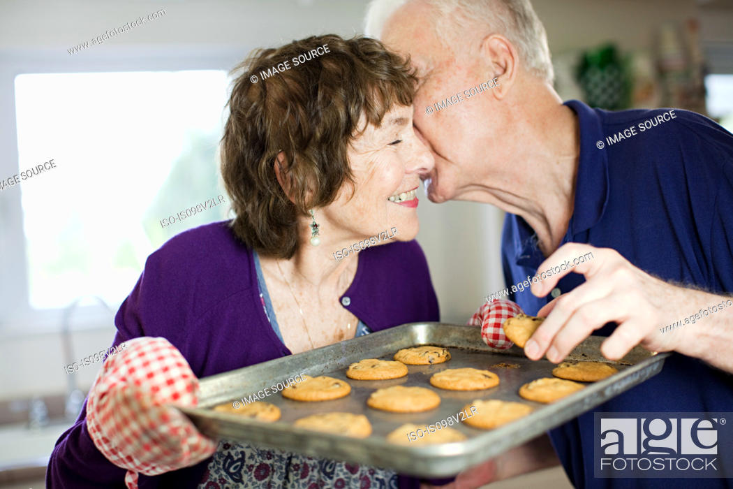 Stock Photo: Senior couple kissing with home baked cookies.