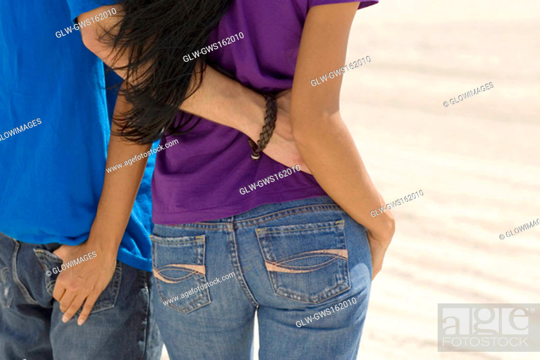 Stock Photo: Rear view of a young couple standing on the beach with their arm around each other.