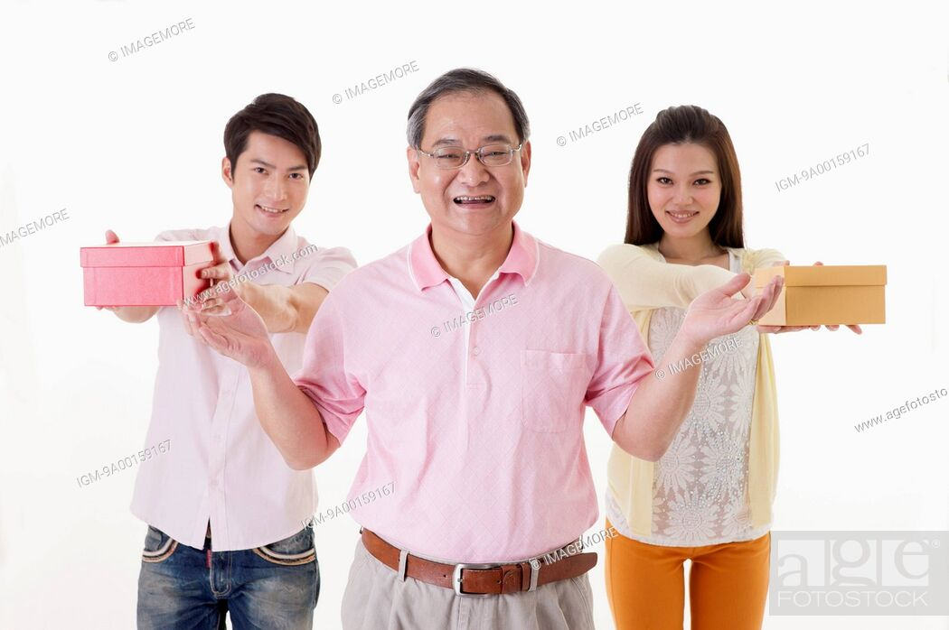 Stock Photo: Family with two children holding gift and smiling at the camera.