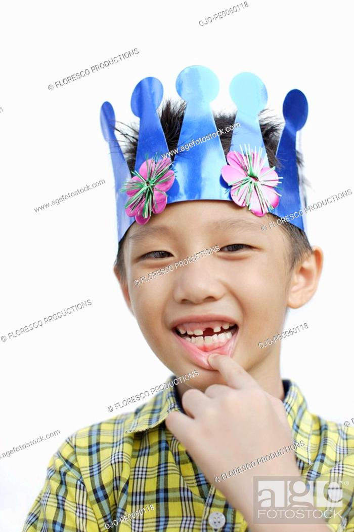 Stock Photo: Young boy indoors wearing party hat and showing missing tooth.